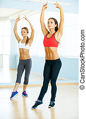 Aerobics class. Two beautiful young women in sports clothing exercising together and smiling