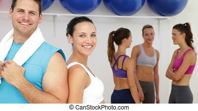 Aerobics instructor and fit brunette smiling at camera...