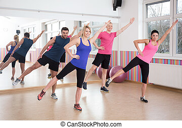 Aerobics on fitness classes - Four young people doing...