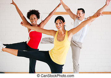 Group of three people in colorful cloths in a gym doing gymnastics
