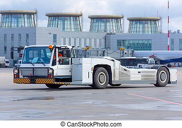 Aerodrome tow tractor is driving along the steering paths at the airport.
