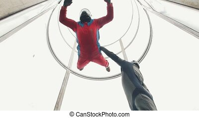 Aerodynamic tube. The wind lifts up the person in red suit....