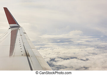 Aeroplane wing detail and cloudy sky. Commercial flight. ...