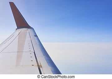 Aeroplane wing over a blue sky background. Flying - ...