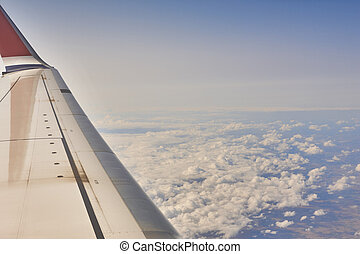 Aeroplane wing over a cloudy blue sky background. Flying - ...