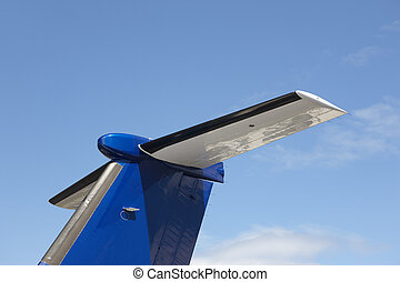 Aeroplane wing tale viewed from below with blue sky. ...