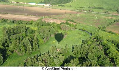 Aerostat cast a shadow on forest near river, view from...