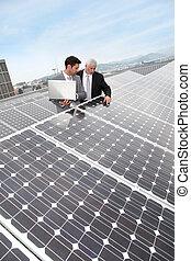 affärsfolk, stående, av, sol, paneler