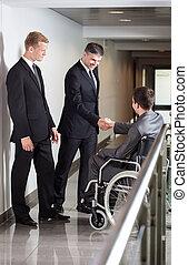 affärsman, på, rullstol, hand skälv, med, co-worker