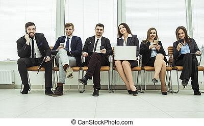 affärsverksamhet lag, med, smartphone, och, laptop, sittande, in, den, påtryckningsgrupp, av, den, nymodig, kontor