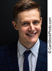 affable and kind well-off male in classic suit look at camera, isolated over black background, smiling
