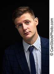 affable and kind well-off male in classic suit look at camera, isolated over black background