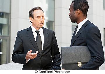 affari, communication., due, fiducioso, uomini affari, parlare, e, gesturing, mentre, standing, fuori