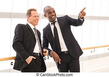 affari, persone., due, allegro, uomini affari, standing, chiudere, a, altro, mentre, uno, di, loro, indicare, lontano, e, sorridente