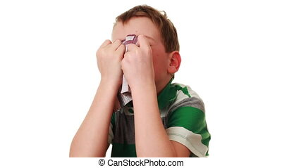 affected by cold boy blowing his nose into handkerchief,...