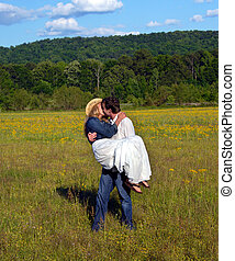 Affection and Landscape - Young man carries wife across...