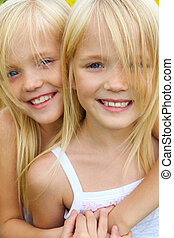 Affection - Portrait of cute girl embracing her twin sister ...