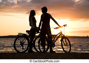 Affection - Young couple standing on seashore with their...