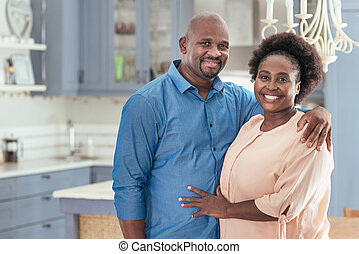 Affectionate African couple standing together in their kitchen