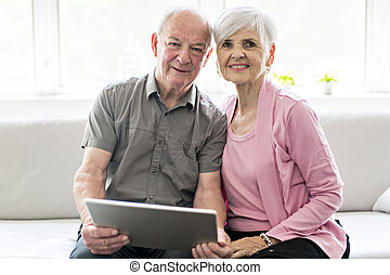 Affectionate attractive elderly couple sitting together on a couch with tablet