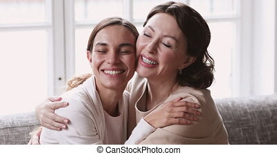 Affectionate beautiful middle aged mother cuddling grown daughter.