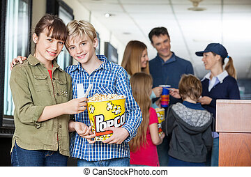 Affectionate Brother And Sister Holding Popcorn At Cinema