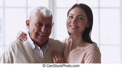 Head shot affectionate cheerful different generations family posing for portrait together indoors. Happy young woman embracing smiling mature senior 80s dad at retirement house, head shot close up.