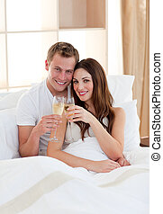 Affectionate couple drinking champagne lying in bed at home