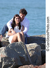 Affectionate couple flirting and hugging on a stone on the beach with the sea in the background