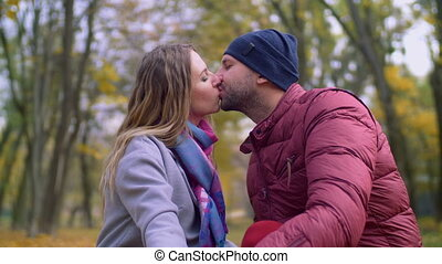 Affectionate couple in tender kiss in autumn park