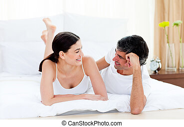 Affectionate couple interacting lying on their bed - Happy...