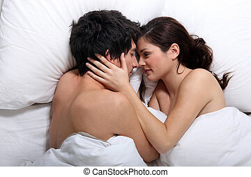 Affectionate couple kissing in bed