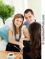 Affectionate couple listen to a saleswoman siting on a sofa...