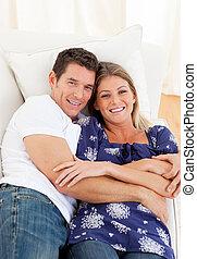 Affectionate couple lying down on sofa
