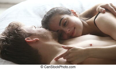 Affectionate couple lying in bed embracing, woman tenderly stroking man