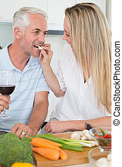 Affectionate couple preparing dinner together and drinking red wine at home in the kitchen