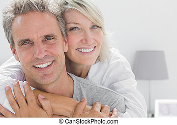 Affectionate couple smiling at camera at home in bedroom