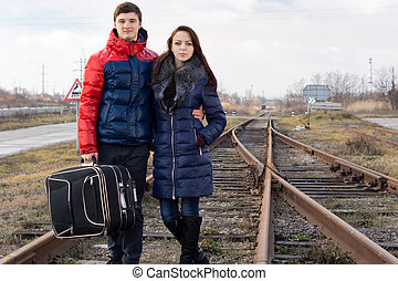 Affectionate couple standing a railway line