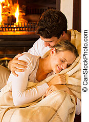 couple wrapped in blanket at home - affectionate couple...