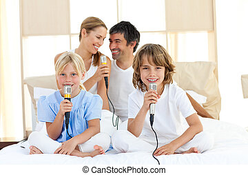 Affectionate family singing together in the bedroom