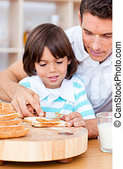 Affectionate father and his son spreading jam on bread - ...