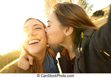 Affectionate friends kissing and taking a selfie