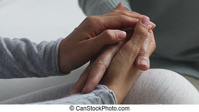 Close up young empathic woman holding stroking wrinkled hands of middle aged mother, showing love care. Affectionate grownup daughter supporting elderly mature mommy, having sincere conversation.