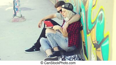 Affectionate hipster urban couple relaxing in town sitting...