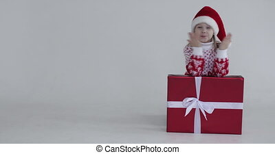Stock video of lovely little girl in Santa hat and winter sweater sending air kisses at camera leaning on Christmas present. Copy space.