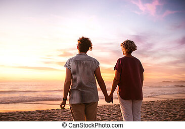 Affectionate lesbian couple holding hands watching a beach sunset