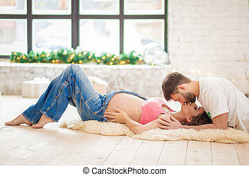 Affectionate man kissing his pregnant wife with baby letters on the belly lying on the sofa at home
