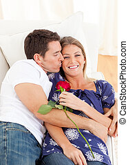 Affectionate man kissing his wife lying on sofa