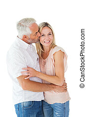 Affectionate man kissing his wife on the cheek on white...