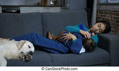 Affectionate mom breastfeeding infant boy on sofa -...